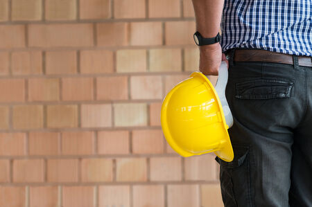 construction safety: Close up Of Male Architect Holding Yellow Helmet At Construction Site