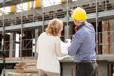 arquitecto: Vista posterior de vista masculino y cliente que miran Bajo Construcción de Edificios