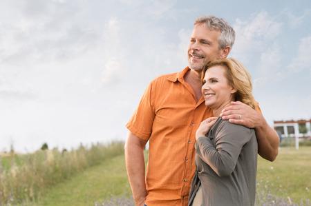 persona de la tercera edad: Retrato de un hombre feliz madura abrazando a su esposa y contemplar el futuro