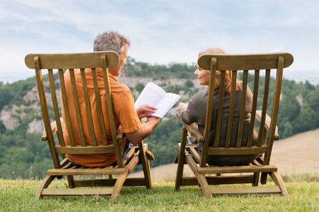 Rear View Of Mature Couple Sitting On Lounge Chair Reading Book photo