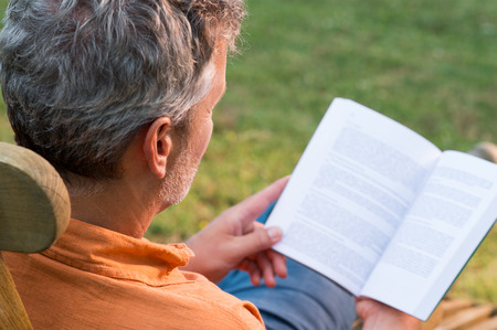 Close-up Of Mature Man Sitting On Lounge Chair Reading Book Outdoor photo