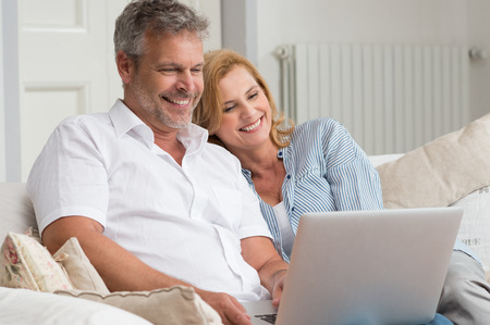 pareja madura feliz: Retrato de pareja feliz madura se sienta en el sof� usando la computadora port�til