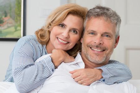 femmes souriantes: Portrait d'un couple d'âge mûr souriant et embrassant à Accueil