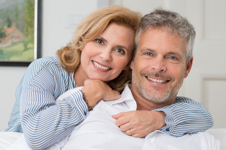 a couple: Portrait Of A Mature Couple Smiling And Embracing At Home Stock Photo