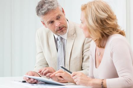 Homme d'affaires d'âge mûr et femme d'affaires Discuter de données Dans Touchpad Au Bureau Banque d'images - 31178906