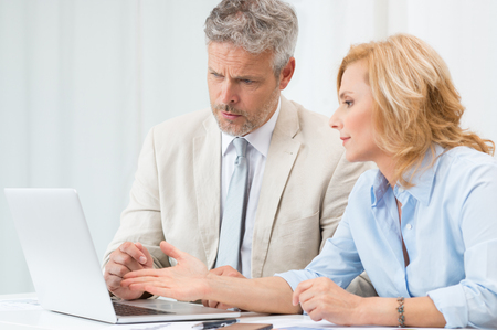 Mature Businessman And Businesswoman Discussing Data In Laptop At Office photo