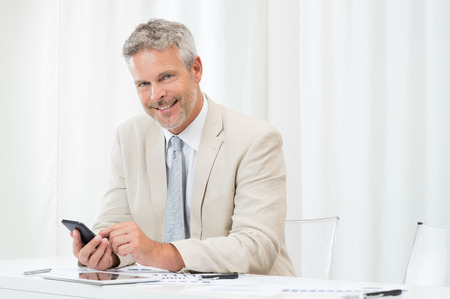 one senior adult man: Happy Smiling Mature Businessman Using Phone At Workplace Stock Photo