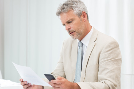 Mature Businessman Working With Papers And Cellphone At Workplace photo