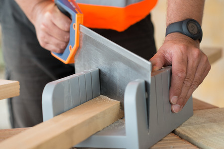 wood craft: Close up Of A Male Carpenter Sawing At Workshop