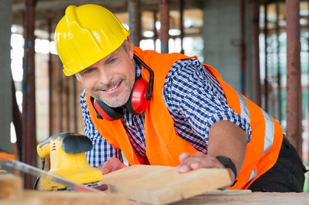 operarios trabajando: Primer plano de un sonriente Hombre Carpintero Mirando a la tabla de madera En Construcción Sitio Foto de archivo