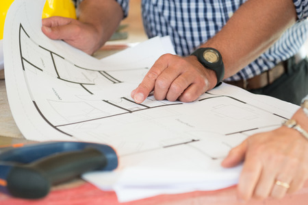 Close-up Of Two People Discussing Plan On Blueprint photo
