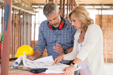 architect: Retrato de vista masculino y mujer madura que discuten un plan en proyecto en la construcci�n del sitio