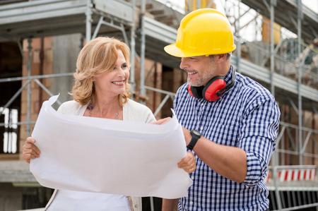 幸せな成熟した女性と男性の建築工事現場の青写真で計画を議論するの肖像画