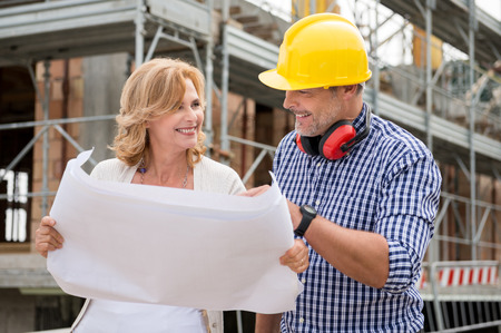 Portrait Of Happy Mature Woman And Male Architect Discussing Plan On Blueprint At Construction Site Stock Photo