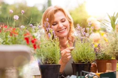 庭の植物を配置幸せの成熟した女性の肖像画
