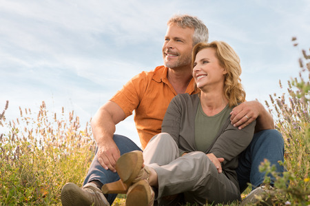 Portrait Of A Happy Mature Couple Sitting In Field And Contemplate The Future Stock Photo