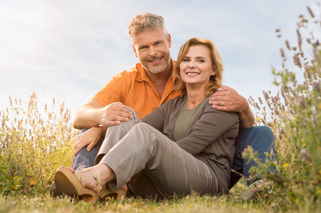 Portrait Of A Happy Mature Couple Looking At Camera Sitting In Field photo
