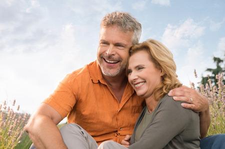 Portret Van Een Gelukkig Rijp Paar zitten in het veld Stockfoto
