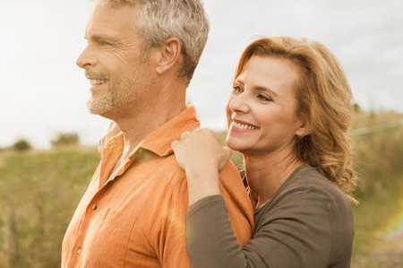 Happy smiling mature couple looking together at the horizon, outdoor photo