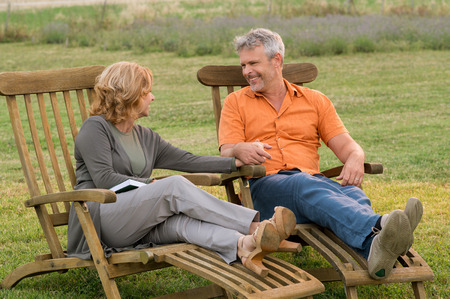 Mature Couple Sitting On Lounge Chair Looking At Each Other Outdoor photo