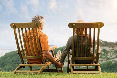 中高年カップル手 Conteplate 未来を保持しているラウンジの椅子に座っての背面図
