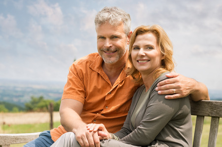 Portrait Of Happy Mature Couple Sitting On Bench Outdoor And Looking At Camera photo