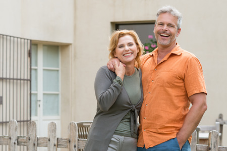 Portrait Of Happy Mature Couple Standing In Front Of House photo