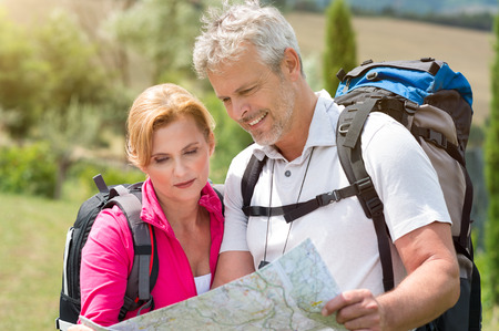 Portrait Of Mature Couple With Backpack Looking At Map photo