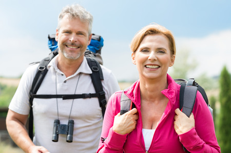 Portrait Of Mature Couple Smiling With Backpack Stock Photo