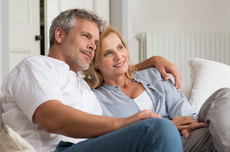 Portrait Of Happy Mature Couple On Sofa Looking At the Future photo