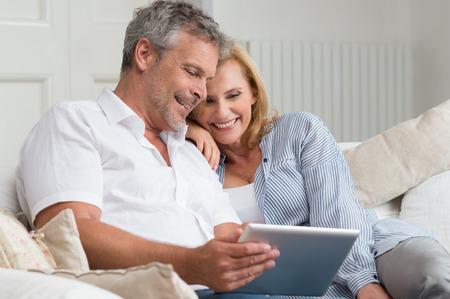 Gelukkig Rijp Paar Zittend Op Bank Met Digitale Tablet