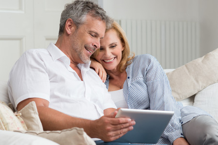 Happy Starsza para siedzi na sofa z cyfrowym tablecie Zdjęcie Seryjne