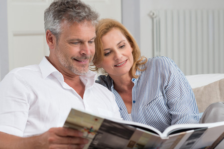 Portrait Of Mature Couple Reading Book Sitting On Couch photo