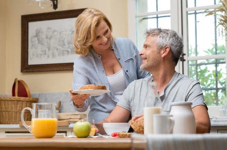 Happy starší žena obsluhující chleba svého manžela na snídani