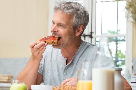 Älterer Mann essen eine frische Scheibe Brot mit Marmelade zum Frühstück