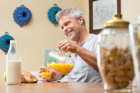 natural juices: Happy Mature Man Pouring Orange Juice Into Glass For Breakfast Stock Photo