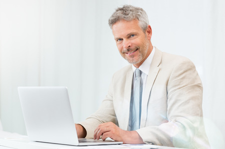 Smiling Mature Businessman In His Office Looking At Camera photo