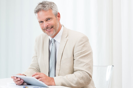 Happy Mature Businessman Looking At Camera And Using Laptop At Workplace photo