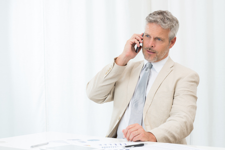Mature Businessman Calling On Mobile Phone In Office photo