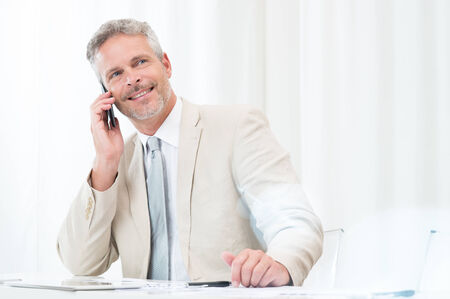 Happy Mature Businessman Using Cellphone At Workplace photo