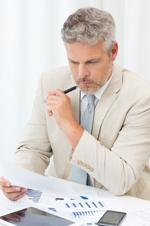 worried businessman: Serious Mature Businessman Concentrating On His Work