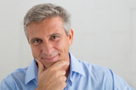 Close-up van lachende volwassen man met hand op kin