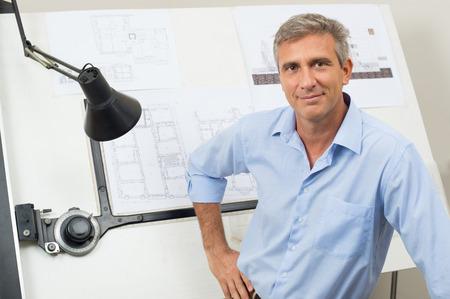 arquitecto: Retrato del arquitecto de sexo masculino con proyecto en la oficina