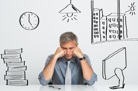 ejecutivo en oficina: Retrato de hombre de negocios nervioso sentado en su escritorio de oficina Foto de archivo