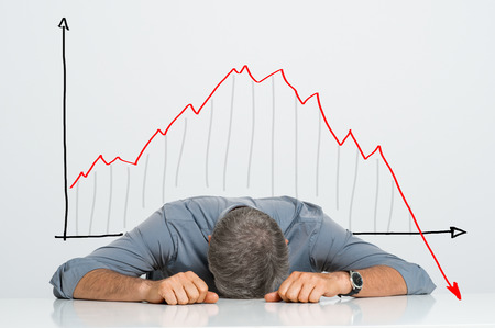 Depressed Businessman Leaning His Head Below a Bad Stock Market Chart Archivio Fotografico