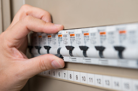 electricity meter: Closeup Of Persons Hand Repair The Switchboard Stock Photo