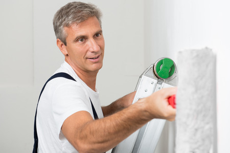 redecorating: Mature Man In Uniform On Stepladder Painting Wall With Roller Stock Photo