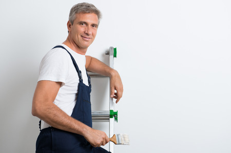 Happy Mature Painter Standing On Stepladder Holding Brush Stock Photo