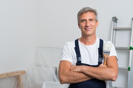 brocha de pintura: Retrato del pintor sonriente con el brazo cruzado que sostiene la brocha en el hogar