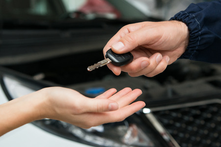 Closeup Of Mechanic Giving Car Key To Customer At Garage photo